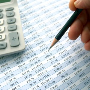 Checking through accounts with pencil and calculator